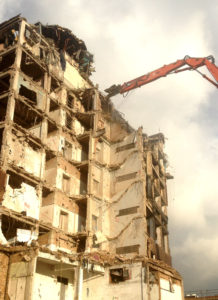 Large crane tearing apart tall building