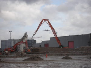 Demolition project with cranes. Aircraft flying in background.