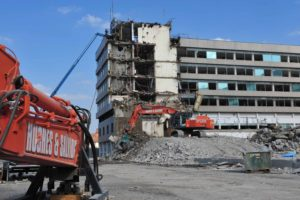 Large building on demolition site being deconstructed by two vehicles.