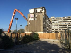 Demolition crane destroying large apartment complex