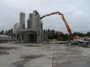 Extended crane demolishing industrial building