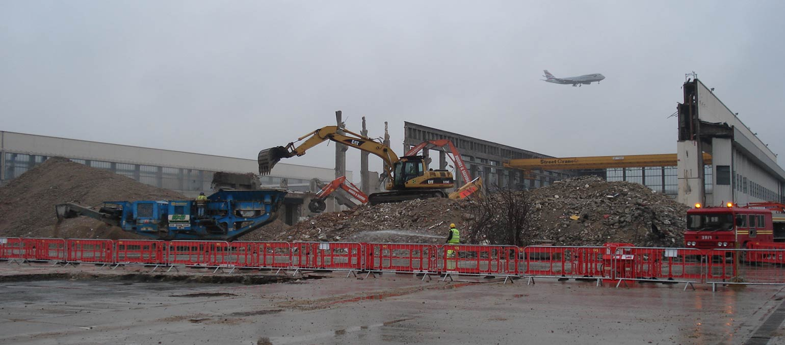 Digger at demolition site. Aircraft taking off in background