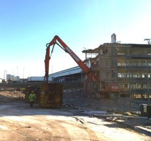 Construction machinery demolishing large building.