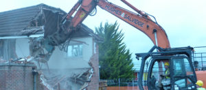 Hughes and Salvidge vehicle demolishing residential building