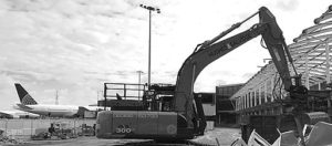 Hughes and Salvidge digger with plane in background. Picture is black and white