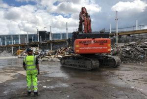 Man in high-vis vest looking at demolition vehicle