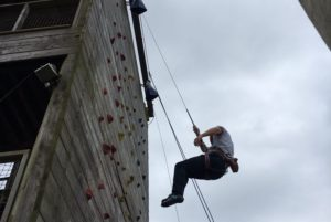 Man abseiling down climbing wall